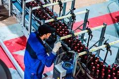 Flaskölproduktion med arbetaren Arkivbild