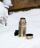 Flask. Hot steaming flask in the snow on the hiking trail Stock Photos