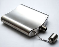 Flask. Metal chrome flask lying on its side with the lid off on a white background stock images