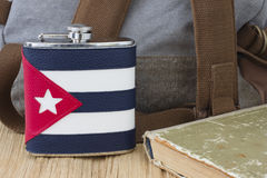 The flask with the Cuban flag. Backpack and old book Royalty Free Stock Photo