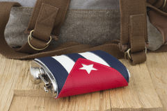 Flask with the Cuban flag and the backpack. The flask with the Cuban flag and the backpack on the wooden table Stock Photography