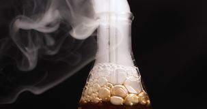 Flask with dark reagent and steam in chemical lab. Close-up view of flask with blue reagent and steam in chemical lab stock footage