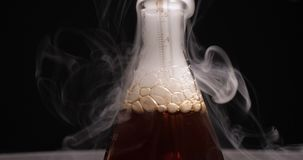 Flask with dark reagent and steam in chemical lab. Close-up view of flask with blue reagent and steam in chemical lab stock video footage