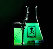 Flask with green poison on black Stock Images