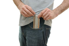 Flask in Guy's Pocket. A guy pulling and uncapping a flask from his pocket Royalty Free Stock Image