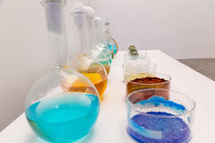 Flask at the laboratory. White laboratory with a table and some flasks with color substances royalty free stock photo