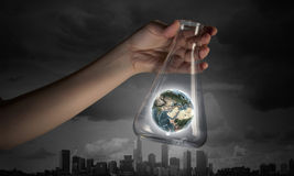 Flask and the objects in it. Hand holds flask with images on varied background. Elements of this image are furnished by NASA Royalty Free Stock Image