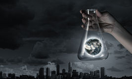 Flask and the objects in it. Hand holds flask with images on varied background. Elements of this image are furnished by NASA Stock Photos