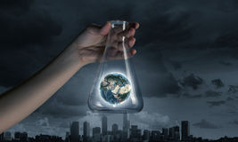 Flask and the objects in it. Hand holds flask with images on varied background. Elements of this image are furnished by NASA Royalty Free Stock Images