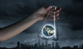 Flask and the objects in it. Hand holds flask with images on varied background. Elements of this image are furnished by NASA Royalty Free Stock Photos