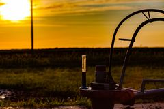 The flask of oil is at the well of the oil pump. Oil quality control. Oil production in Russia. Sunset. The flask of oil is at the well of the oil pump. Oil stock images