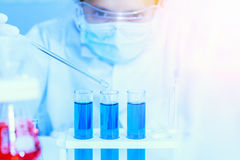 Flask in scientist hand with test tubes for analysis. Royalty Free Stock Photos
