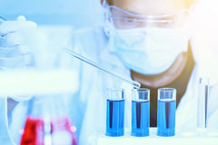 Flask in scientist hand with test tubes for analysis. Royalty Free Stock Photography