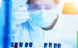 Flask in scientist hand with test tubes for analysis. Royalty Free Stock Image