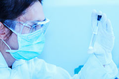 Flask in scientist hand with test tubes for analysis. Royalty Free Stock Photo