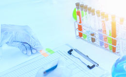 Flask in scientist hand with test tubes for analysis. Stock Photography