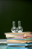 Flask and textbooks on the desk Royalty Free Stock Images