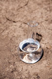 Flask with water on cracked soil Stock Photos