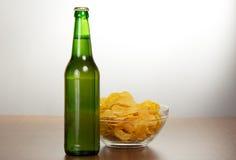 Flaska av öl och chiper royaltyfri fotografi
