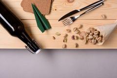 Flaska av öl- och pistaschmuttermellanmålet på trätabellen Lekmanna- lägenhet, kopieringsutrymme Arkivfoto