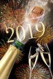 Flaska av champagne med flygkork och fyrverkerit på Silvester 2019 royaltyfri fotografi