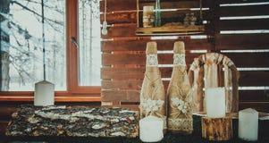 Flaska av champagne, vita stearinljus, på en mörk träbakgrund Royaltyfria Bilder