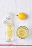 Flaska av citronvatten och exponeringsglas Arkivbilder