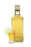 Flaska av den guld- tequilaen och skottet med limefruktskivan Royaltyfria Foton