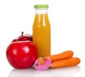 Flaska av fruktsaft, äpplen, morötter och attrappen som isoleras på vit royaltyfri foto
