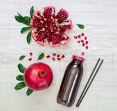 Flaska av granatäpplefruktsaft och granatäpplen Arkivfoton