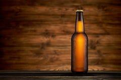Flaska av kallt öl på trätabellbakgrund fotografering för bildbyråer