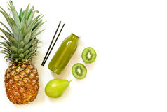 Flaska av kiwi, ananas, päronfruktsaft som isoleras på vit, och ingredienser Arkivfoton