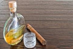 Flaska av konjak med cigarren och exponeringsglas Arkivfoto