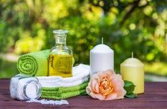 Flaska av nödvändig det salta olja och havet stearinljus steg torkade för tvålbrunnsort för vallmo set behandlingar för handduk royaltyfri bild