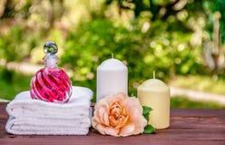 Flaska av nödvändig olja, mjuka handdukar och stearinljus torkade för tvålbrunnsort för vallmo set behandlingar för handduk arkivfoto