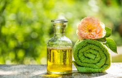 Flaska av nödvändig olja och den mjuka handduken Grön mjuk nödvändig olja för handduk och för ros Tvål-, handduk- och blommasnowd royaltyfri foto