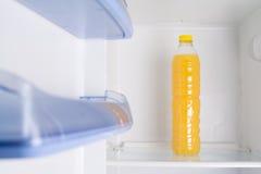 Flaska av ny orange fruktsaft i en kyl Fotografering för Bildbyråer