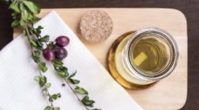 Flaska av olivolja och örter på den lekmanna- skärbrädalägenheten Arkivfoto