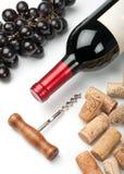 Flaska av rött vin, druvor, korkskruv och korkar Fotografering för Bildbyråer