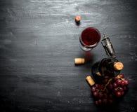 Flaska av rött vin med en korkskruv Fotografering för Bildbyråer