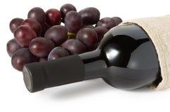 Flaska av rött vin och druvor Royaltyfri Fotografi