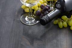 Flaska av rött vin, tomt exponeringsglas och druvor på träbakgrund Royaltyfri Bild