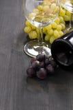 Flaska av rött vin, tomt exponeringsglas och druvor på träbakgrund Fotografering för Bildbyråer