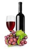 Flaska av rött vin, wineglass och druvor arkivfoto