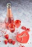 Flaska av rosa champagne, exponeringsglas med nya jordgubbar och den hjärta formade gåvan royaltyfri bild