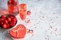 Flaska av rosa champagne, exponeringsglas med nya jordgubbar och den hjärta formade gåvan arkivfoto