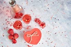 Flaska av rosa champagne, exponeringsglas med nya jordgubbar och den hjärta formade gåvan arkivfoton