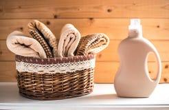 Flaska av tvättmedel och handdukar i korg arkivfoto