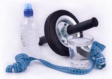 Flaska av vatten, exponeringsglas av vatten, rullhjul för abdominals och Arkivbild