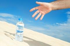 Flaska av vatten i öknen Arkivbild